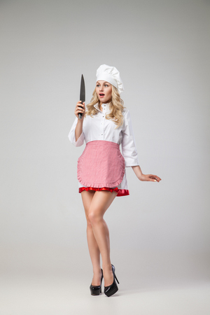 holding a knife: Portrait of beautiful blonde woman with long hair in uniform looking at sharp knife in shock.Studio shot.