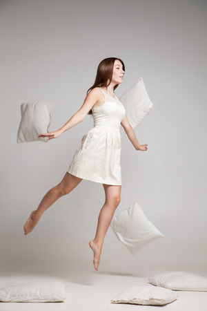 weightless: Studio shot of weightless woman jumping with flying pillows. Stock Photo