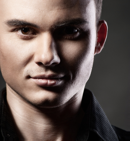 visage homme: Gros plan portrait d'un modèle masculin sexy sur fond gris foncé Banque d'images