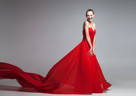 lady in red: Portrait of beautiful blonde woman in bright red dress with flying skirt.Studio shot