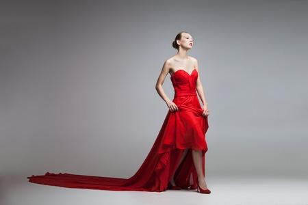 Ritratto di modello biondo camminare in abito rosso con lunga colpo skirt.Studio