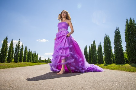 barefoot blonde: Portrait of blonde young barefoot woman in pink princess dress on alley in sunlight Stock Photo
