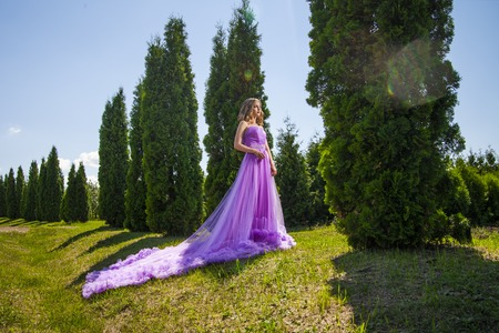long skirt: Blonde lady in violet dress with long skirt near row of green trees in sunlight Stock Photo