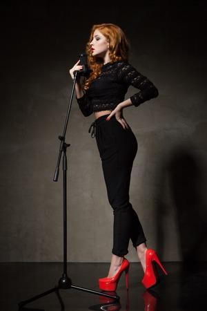 tacones rojos: Retrato de mujer de pelo rojo en negro y rojo zapatos de tacón alto que firman canción mic.Studio disparo