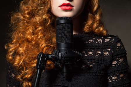 unrecognizable: Close-up of unrecognizable red-haired woman singing in black mic