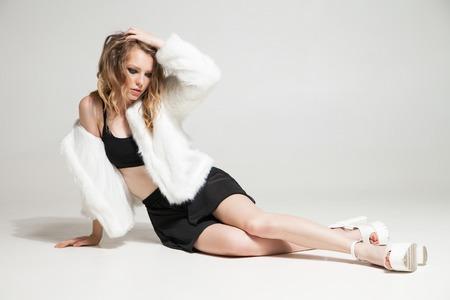 manteau de fourrure: mod�le � la mode dans le manteau de fourrure regardant vers le bas tout en restant assis sur floor.Studio tir
