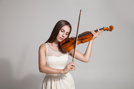 Studio shot of brunette in white dress plays violin.White background Stock Photo