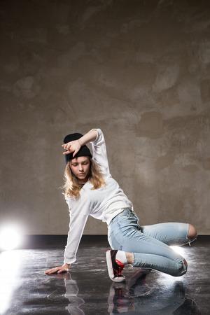 street shot: Portrait of young woman performing street dance.Studio shot