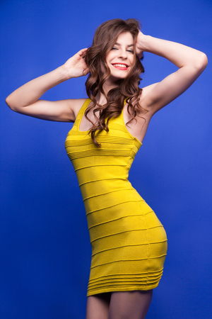 yellow dress: Portrait of attractive young girl in yellow dress posing with smile on blue background.Isolate