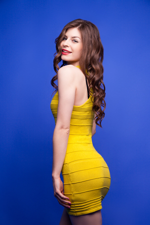 yellow dress: Portrait of attractive and smiling brunette girl in yellow dress posing at camera on blue background.Isolate Stock Photo