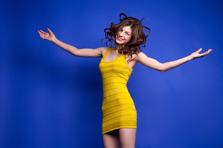 flying hair: Portrait of beautiful smiling model with flying hair jumping with arms widened on blue background.Isolate
