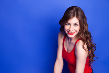 Portrait of beautiful young model in red top and red lips smiling at camera.Isolate.Blue background Stock Photo