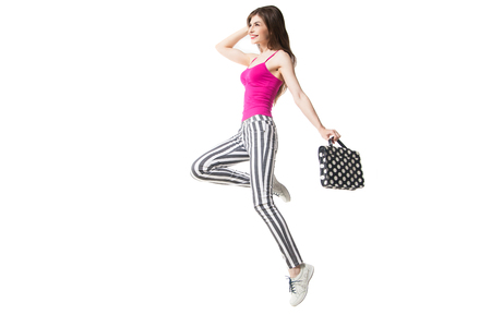 side view of happy brunette model in striped legging and pink with polka dot bag. Isolate. Stock Photo