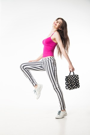 legging: side view of happy brunette model in striped legging and pink with polka dot bag. Isolate. Stock Photo