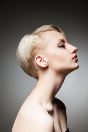 side shot: Side view of sensual and dreaming blonde model with hairstyle and make-up with eyes closed.Studio shot.