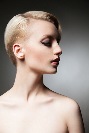 half face: Half face of calm young model with short blonde hair and make-up with bare shoulders looking down.Studio shot.