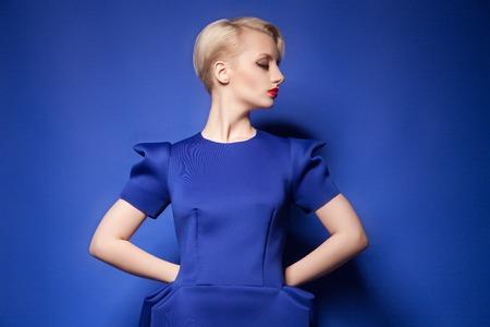 blue dress: Studio shot of elegant model in blue dress posing on blue background.Isolate