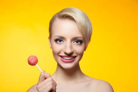 vibrant background: Portrait of pretty smiling blondie with bright lollipop on yellow background