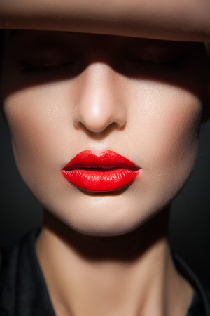 people shadow: Close-up of young model with eyes closed, red lips and perfect smooth skin in flash light