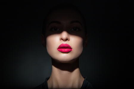 half face: Portrait of beautiful woman with bright lips and half face covered in shadow