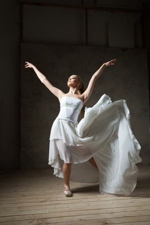 Elegant ballerina in white dancing with arms outstretched and flying skirt in studio