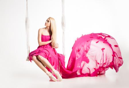 Retrato de rubia bailarina en zapatillas de ballet y hermoso vestido rosa con falda de vuelo en el oscilación