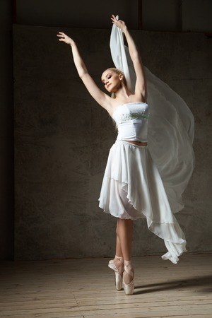 pointes: Portrait of blonde ballet dancer with arms up dancing on pointes in studio