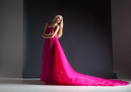 Elegante donna bionda posa in bella rosa brillante e abito lungo in studio su sfondo grigio.
