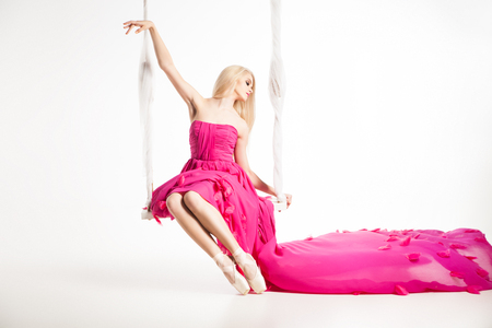 pink dress: Portrait of blonde ballerina in ballet shoes and beautiful pink dress with flying skirt on swing
