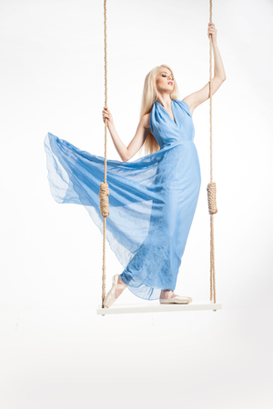 blue dress: Portrait of beautiful young ballerina standing on swings in blue dress and pointes.Isolated.