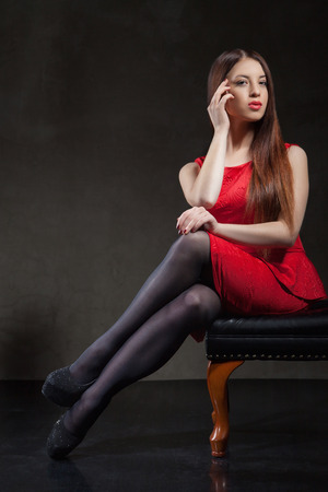 close p: A close up of beautiful model girl  sitting on a  chair in studio wearing a short red dress, black tights  and black high heels shoes with long hair and beautiful make-up p.
