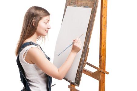 Sourire, femme peintre au pinceau assis à chevalet dessin avec des peintures acryliques