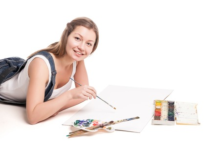 drawing pad: Young woman happily lies on the floor drawing in her note pad.  On a white background.