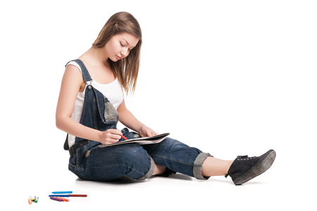 Young woman happily sitting on the floor drawing in her note pad.  On a white background.