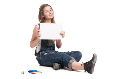 Young smiling woman  sitting  on the and show her note pad.  On a white background.