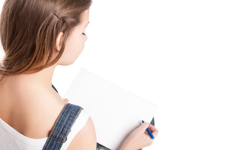 drawing pad: Young woman  drawing in her note pad.  On a white background. Stock Photo