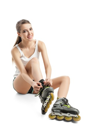 rollerskates: Pretty happy girl with rollerskates sitting on floor Stock Photo