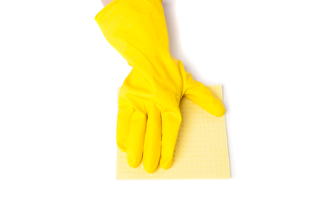 Arm in yellow rubber gloves removes dust from surface with yellow duster. Studio isolated photo