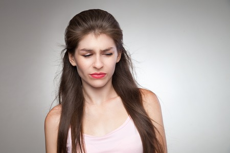 desprecio: Mujer molesta sensación culpable. Con un poco de desprecio en su cara. retrato de estudio sobre fondo gris viñeta. Foto de archivo