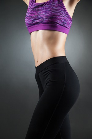 droppings: Fit anonymous sport-girl in black yoga pants and purple top with heat droppings on abdominal muscles. Studio portrait black background.