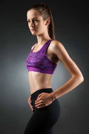Fit sport-girl in black yoga pants and purple top with some sweat on her body. Studio portrait black background. Stock Photo