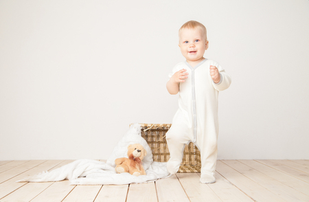 Toddler in white outfit standing and smiling at camera with bucket and bear around on white . Stock Photo