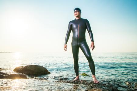 Mann im Taucheranzug stehen im Sonnenuntergang an der Küste in Wellen und Wegschauen.