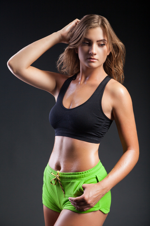 Athletic young girl wearing black sport top and green shorts posing and looking down on black background.