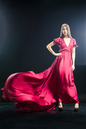 Portrait of elegant blonde woman with long blonde hair in bright pink dress.Studio shot