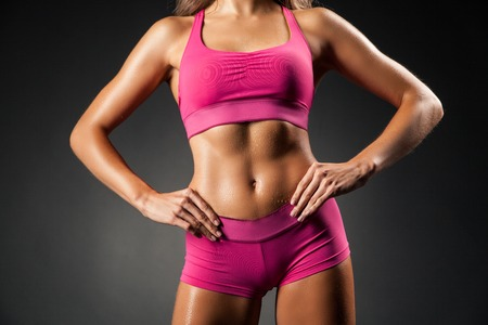 female fitness: Crop faceless studio shot of fit female in short pink sportswear posing with hands on hips seductively. Stock Photo