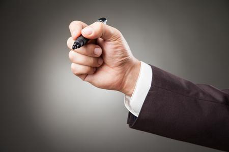 and the horizontal man: Hand of man wearing suit holding black marker. Horizontal studio shot