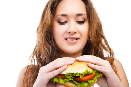beefburger: Happy Young Woman Eating big yummy Burger isolated Stock Photo