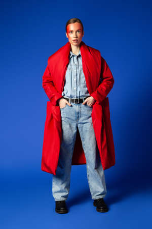Confident female model in baggy clothes against blue background
