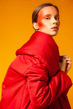 Young woman wrapping in red coat against yellow background